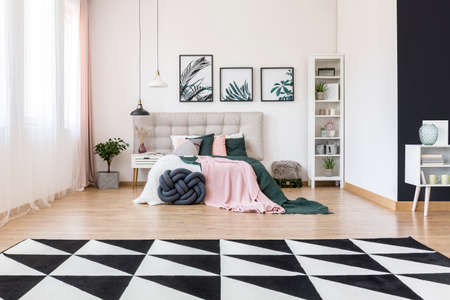 Photo pour Black and white carpet and plant in spacious bedroom interior with pink and green bedsheets on bed with beige bedhead - image libre de droit