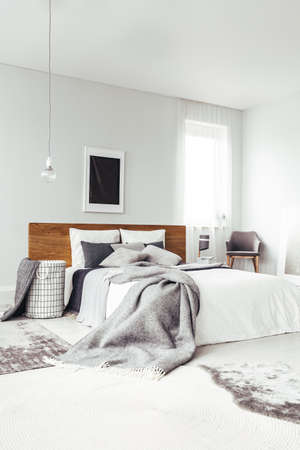 Photo pour Black poster on white wall with copy space above king size bed in bright bedroom interior with chair and window - image libre de droit