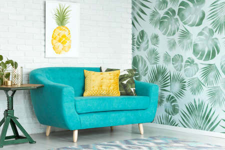 Photo pour Yellow pillow on turquoise couch against brick wall with pineapple poster in sitting room with leaves wallpaper - image libre de droit