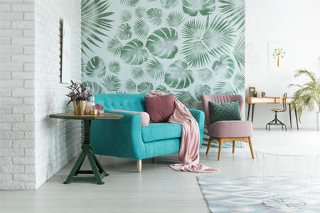 Foto de Green table with plant next to blue sofa and pink armchair with pillow against green wallpaper in living room - Imagen libre de derechos