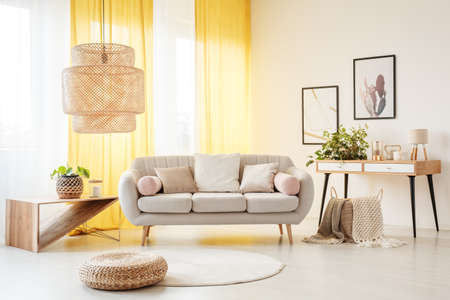 Foto de Rattan lamp above pouf and carpet in bohemian living room with settee, plants and yellow curtains - Imagen libre de derechos
