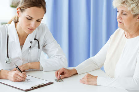 Photo pour Professional doctor with stethoscope writing prescription for dietary supplements to a patient - image libre de droit