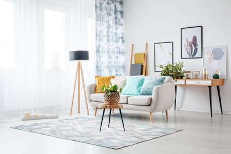 Foto de Stool with plant on carpet and lamp in living room with posters above cabinet behind sofa with blue cushion - Imagen libre de derechos