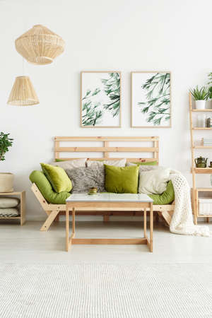 Photo pour Posters with plants hanging on white wall in stylish living room interior with green lounge and wooden table - image libre de droit