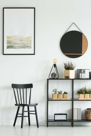 Photo for Classic black chair and shelf with plants against white wall with painting and round mirror in bright room - Royalty Free Image