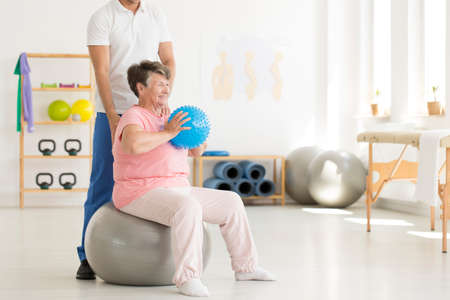 Photo pour Happy senior woman sitting on grey ball and holding blue ball while exercising at gym - image libre de droit