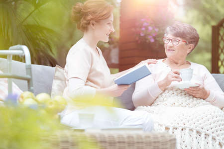 Photo pour Old woman talking to a young caregiver reading a book during meeting on a terrace - image libre de droit