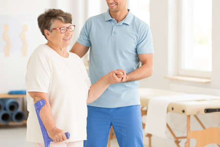 Photo pour Smiling physiotherapist supporting disabled elderly woman after injury - image libre de droit