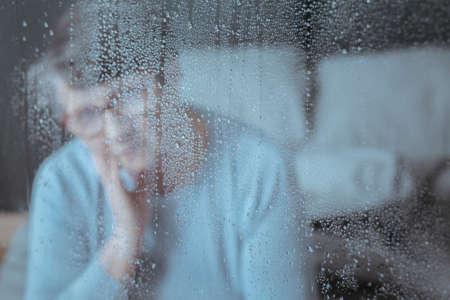 Foto de Close-up of raindrops on window with sad senior woman in the background - Imagen libre de derechos
