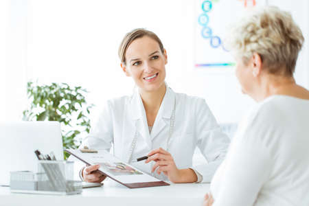 Photo pour Smiling nutritionist showing a healthy diet plan to female patient with diabetes - image libre de droit