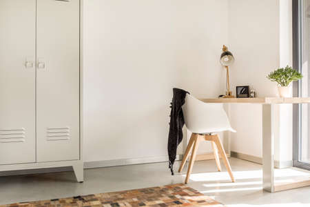 Photo pour White wooden chair with black blanket standing by the desk with lamp and potted plant - image libre de droit