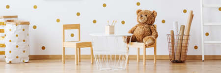 Foto de Mustard and white dotted nursery with teddy bear, metal table and wooden chairs - Imagen libre de derechos
