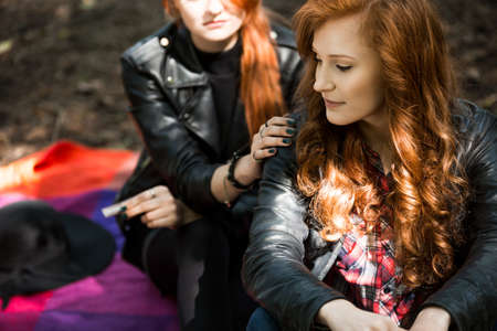 Foto de Red-haired rebellious girl in leather jacket with girlfriend during teenager's meeting in the forest - Imagen libre de derechos