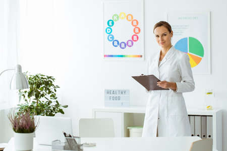 Photo pour Professional nutritionist in white uniform in the office with plant and colorful posters - image libre de droit