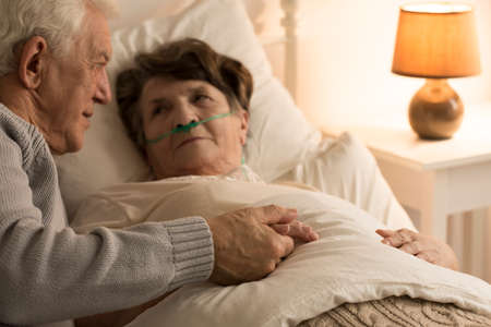 Foto de Elderly man supporting his sick wife lying in bed at home - Imagen libre de derechos