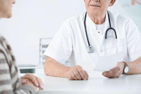 Photo pour Close-up of doctor with stethoscope giving prescription to a weak patient - image libre de droit