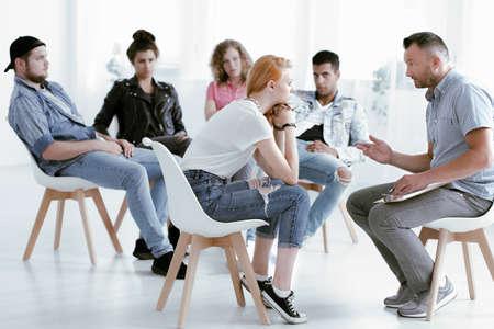 Foto de Counselor talking with young rebellious girl during group therapy - Imagen libre de derechos