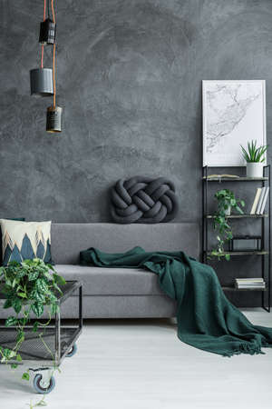 Photo pour Dark green blanket on grey sofa against concrete wall in guy room interior with designer lamp and map poster on the wall - image libre de droit