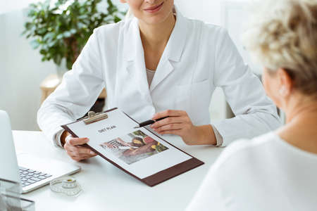 Photo pour Close-up of nutritionist holding a personalized diet plan for a patient during appointment in the clinic - image libre de droit