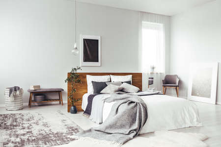 Foto de Dark poster on the wall with copy space in bright bedroom interior with bench, grey chair and patterned carpet - Imagen libre de derechos
