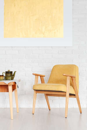 Foto de Retro yellow chair next to a wooden table with kettle against white brick wall with gold painting in dining room interior - Imagen libre de derechos
