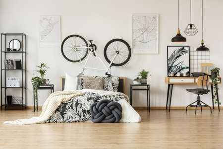 Foto de Wooden chair against desk in trendy black and white bedroom for teenager with bike, plants and patterned decorations - Imagen libre de derechos