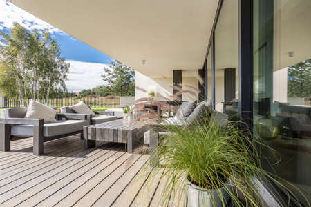 Photo pour Grey garden furniture on board floor on terrace of spacious apartment with view of neighborhood - image libre de droit