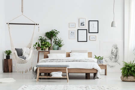 Foto de Hammock with blankets near plant on wooden stool and bed with white bedding in natural bedroom interior with posters - Imagen libre de derechos