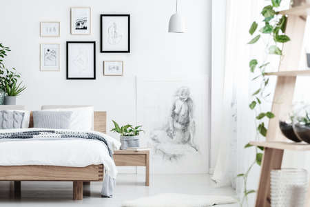 Foto de Drawing on white wall of simple bedroom interior with plant on wooden nightstand next to a bed with pillows - Imagen libre de derechos