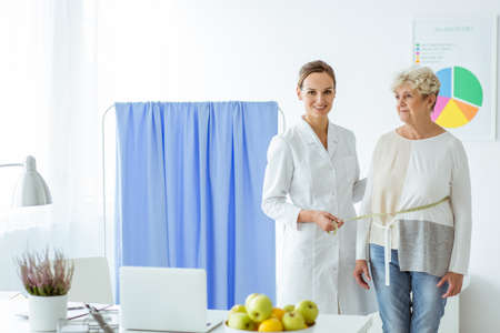 Foto per Smiling nutritionist measuring patient on diet in the office to check progress - Immagine Royalty Free