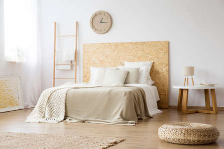 Foto de Pouf, rug and ladder in natural bedroom with brown blanket on bed against white wall with clock - Imagen libre de derechos