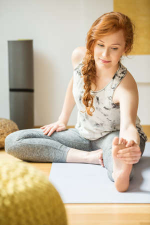 Photo for Young woman with a ponytail stretching on the floor during yoga class - Royalty Free Image