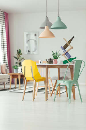Foto de Bottles on rack and kettle on wooden table in dining room interior with lamps and mint and yellow chair - Imagen libre de derechos