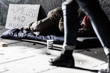 Foto de street person in sleeping-bag begging for money and food - Imagen libre de derechos