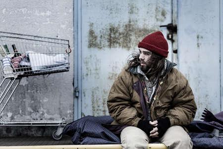 Foto de Dirty beggar sitting on a night-bag next to a metal trolley with bottles. Homeless living conditions concept - Imagen libre de derechos