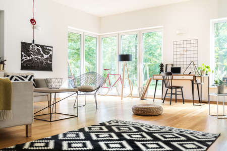 Foto de Black and white carpet and pouf in multifunctional living room with workspace, lamps and poster - Imagen libre de derechos