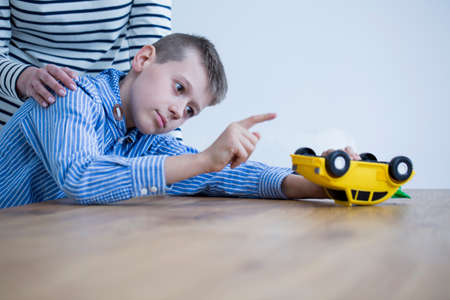 Foto de Kid with Heller syndrome playing with a yellow toy and his mother encouraging him - Imagen libre de derechos