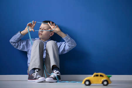 Foto de Autistic child playing with a string and a yellow toy car against a blue wall with copy space - Imagen libre de derechos