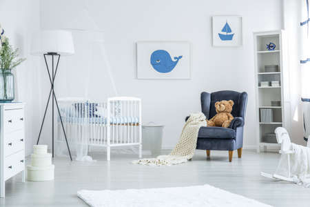 Photo pour White crib standing between a navy blue armchair and oversized lamp in cozy nursery with nautical design - image libre de droit