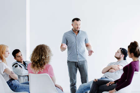 Foto de Psychotherapist speaking to difficult teenagers sitting in a circle in a white office with copy space - Imagen libre de derechos