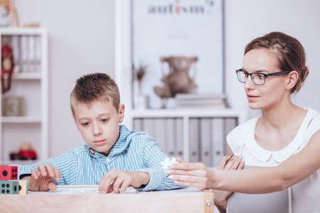 Foto de Professional teacher trying to encourage autistic kid to play in the classroom - Imagen libre de derechos