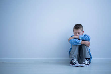 Foto de Alienated boy sitting alone on the floor against a wall with copy space. Sad child with autism concept - Imagen libre de derechos