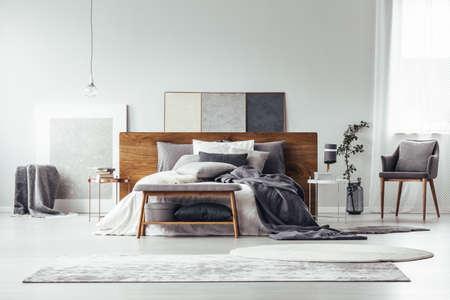 Foto de Gray and white rugs in monochromatic bedroom interior with wooden bed, bench and armchair - Imagen libre de derechos