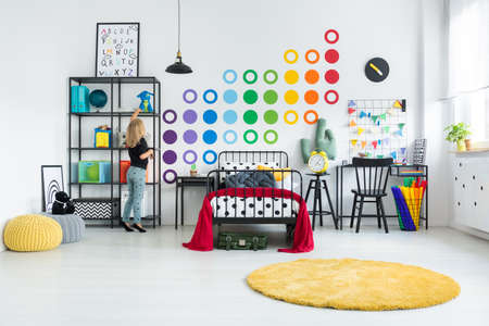Photo for Blonde girl tidying her colorful room with dot stickers on the white wall and round yellow rug - Royalty Free Image