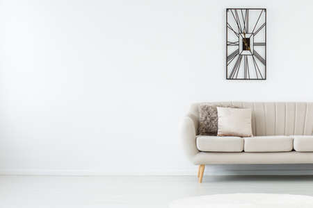 Photo for Empty white room with grey sofa and metal black clock on the right - Royalty Free Image
