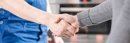 Photo pour Close-up of expert and client shaking hands after repairing the fault - image libre de droit