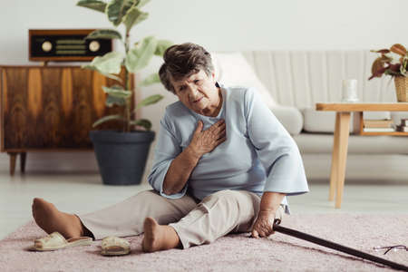 Photo for Disabled elder lady sitting on the floor with a walking stick and holding her chest after falling down - Royalty Free Image