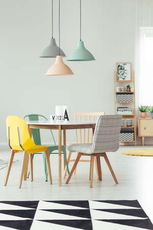 Foto de Peach, mint and grey lamp above round table and yellow chair in dining room interior with black and white carpet - Imagen libre de derechos