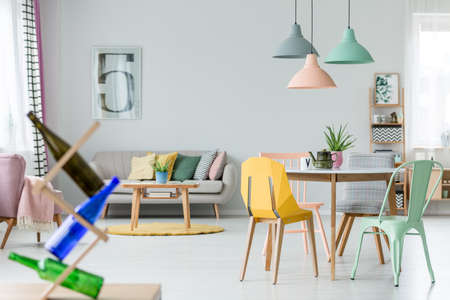 Photo pour Mint and yellow chair at table with kettle under pastel lamps in spacious flat interior with cushions on sofa near yellow round carpet - image libre de droit