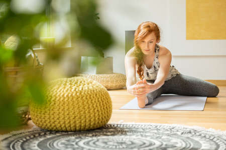 Foto de Active woman exercising on the floor at her home with yellow decorations - Imagen libre de derechos